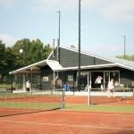 Het clubhuis gezien vanaf de tennisbanen, met zicht op het zij-terras,