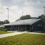 De achterkant van het tennispaviljoen met het hele dakvlak bedekt met zonnepanelen.